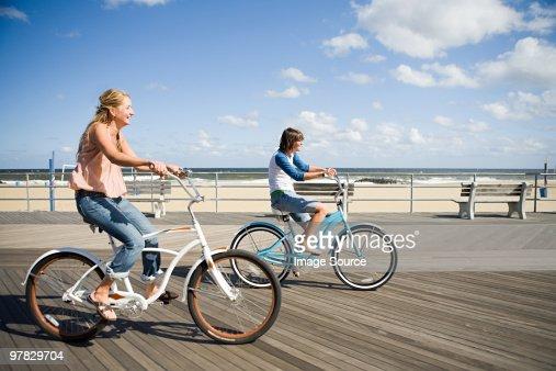 Two women cycling on boardwalk