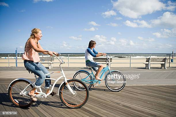 Two women cycling on boardwalk