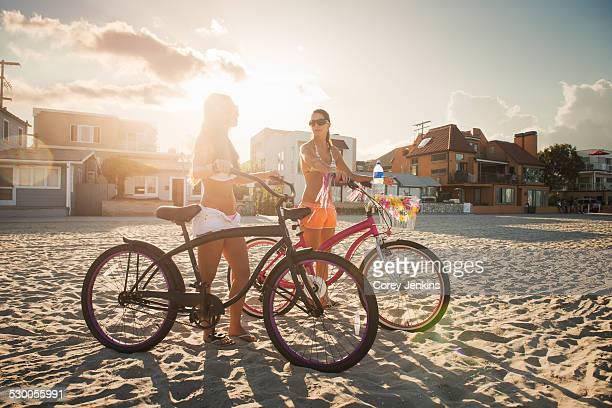 Two women cyclists chatting on beach, Mission Bay, San Diego, California, USA