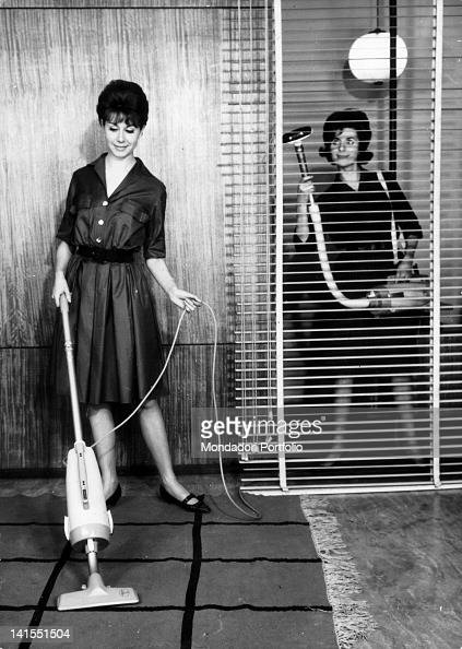 Two women demonstrate the different uses of a 'Hoover' vacuum cleaner one cleans a carpet the other a Veneian blind 1960s