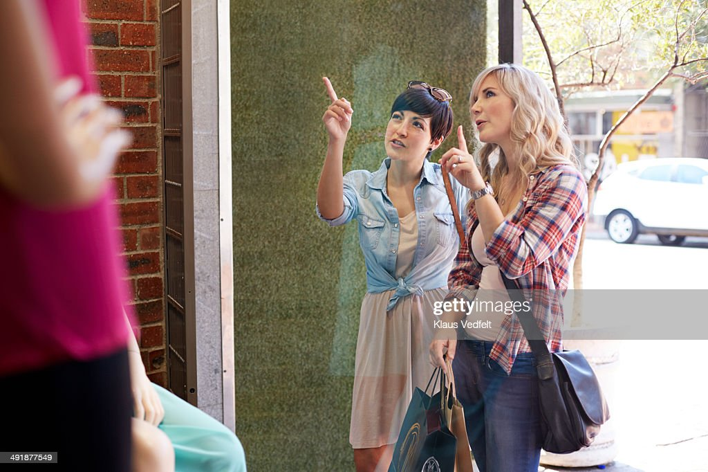 Two women discussing, while window shopping : Stock Photo