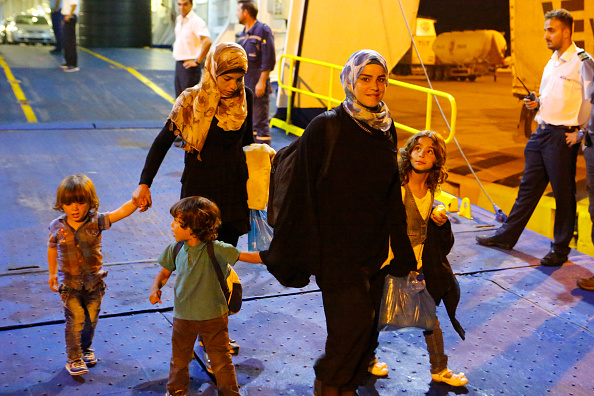 Two women disembark with their children from the Tera Jet...