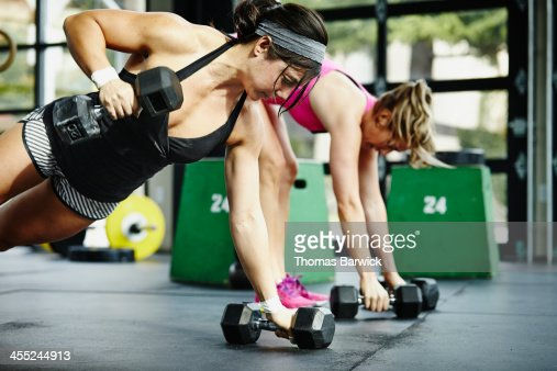Two women doing pushups with dumbbells in gym : Stock Photo