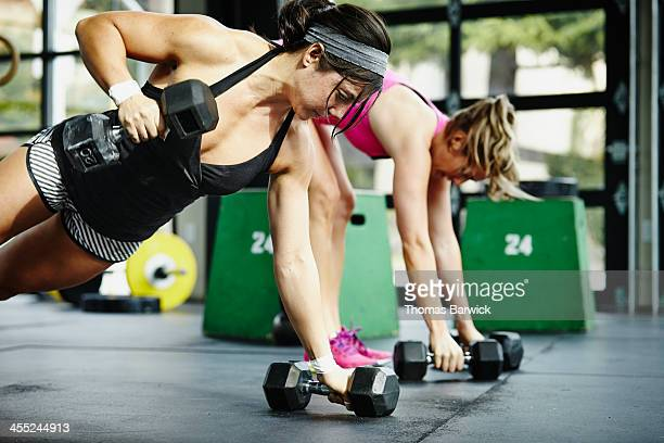 Two women doing pushups with dumbbells in gym