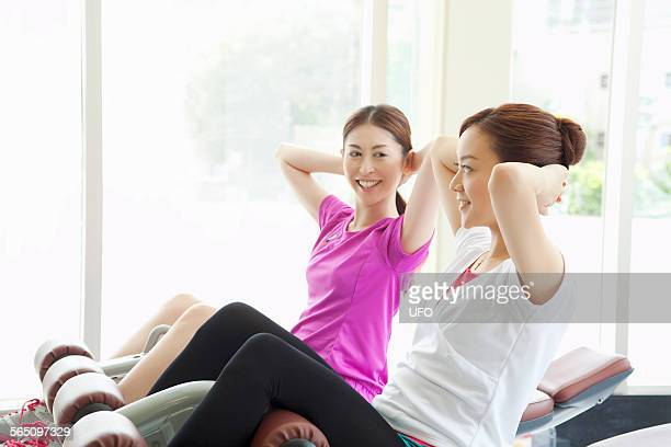 Two women doing sit-ups in gym