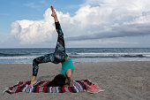 Two Young Women doing yoga exercises on the beach in yoga pants and tank tops
