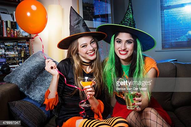 Two women dressed as witches on sofa.
