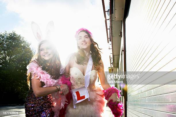 two women dressed for hens party running on street