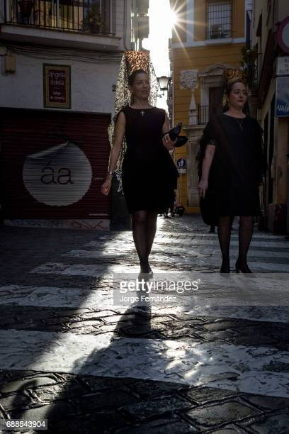 Two women dressed in a very old fashion way with the traditional 'mantilla' and 'peineta' walking in the streets In Seville during what is known as...