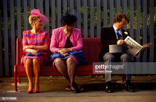 Two women dressed in bright pink sit on a station bench enroute to Ascot racecourse on Ladies Day at Royal Ascot racing week A man with top hat and...