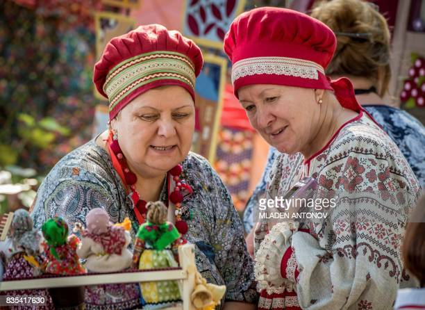 Two women dressed in costume examine dolls on August 19 2017 in Yekaterinburg during celebrations for the 294th anniversary of the city Yekaterinburg...