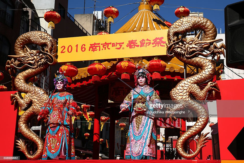 Two women dressed in traditional Chinese costumes perform in celebration of the Chinese New Year on a stage at the Nankinmachi square, China Town on February 8, 2016 in Kobe, Japan. In Nankinmachi, the district known as Kobe Chinatown, tourists enjoyed Chinese food, lion dance and the parade organized to celebrate the Lunar New Year.