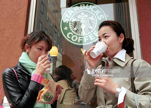 Two women drink Starbucks coffee March 17 2001 outside a Starbucks Coffee shop in Tokyo Japan Since opening its first store in Japan in August 1996...