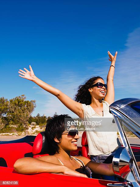 Two women driving in red convertible