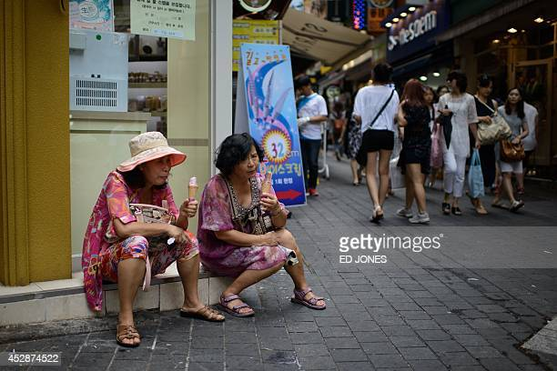 Two women eat ice cream as they sit along a street in the popular Myeongdong shopping area of central Seoul on July 29 2014 South Korea logged a...