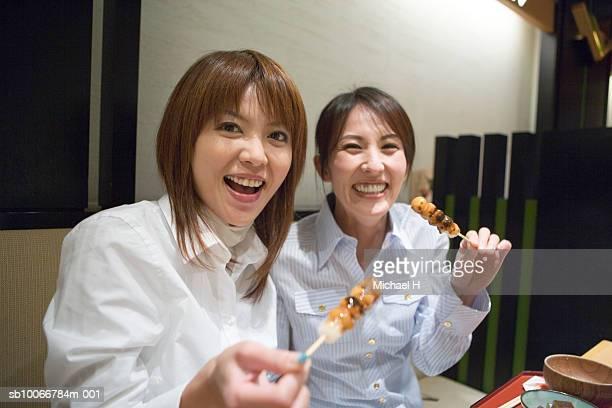 Two women eating dumplings, portrait