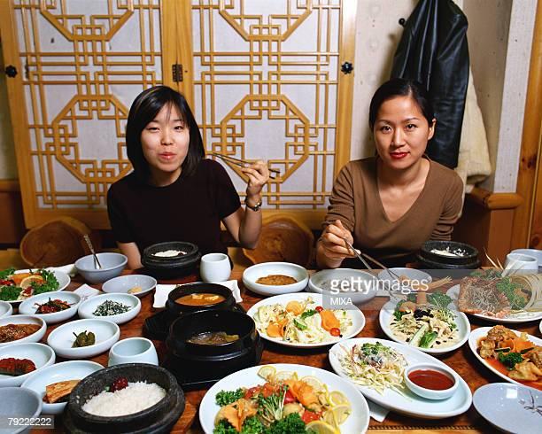 Two women eating Korean food