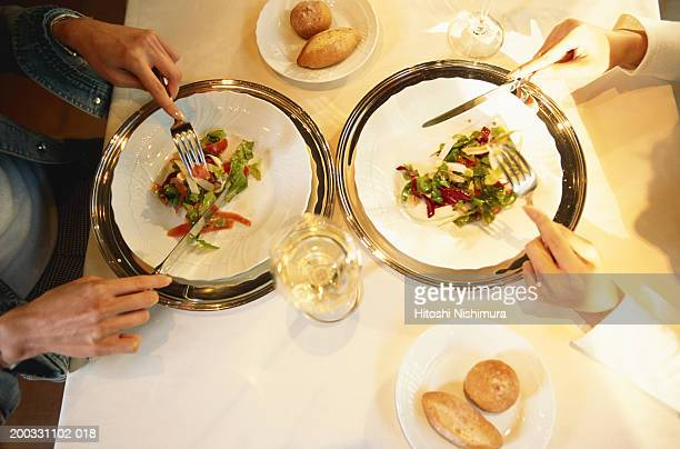 Two women eating salad at restaurant table, overhead view
