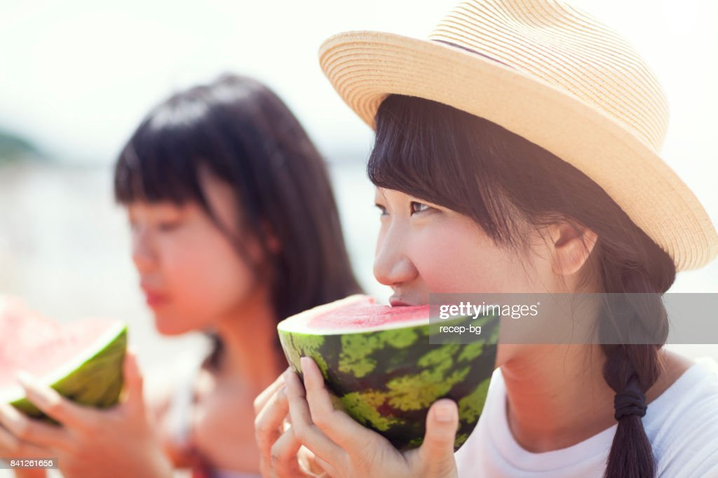 Two Women Eating Watermelon On The Beach : Stock Photo