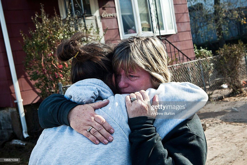 Two women embrace while crying in the Midland Beach neighborhood of Staten Island on November 3, 2012 in New York City. As clean up efforts from Superstorm Sandy continue, colder weather and another storm predicted for next week are beginning to make some worried.