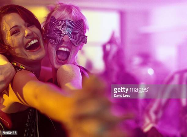 Two women embracing at office party, one wearing mask, portrait