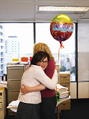 Two women embracing in office