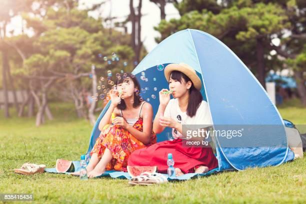 Deux femmes appréciant soufflant des bulles en été