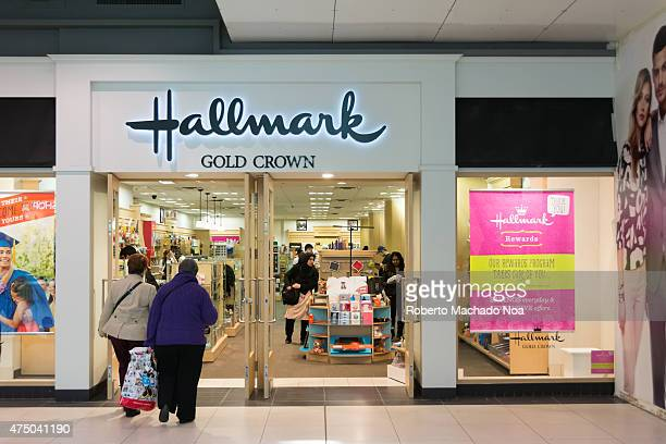 Two women entering Hallmark branch inside the mall with a pink poster on the glass window promoting the store's rewards program