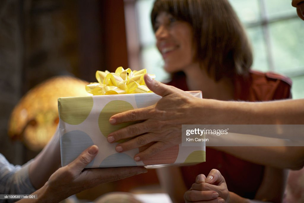 Two women exchanging gift over table, close-up of hands, out of focus woman in background