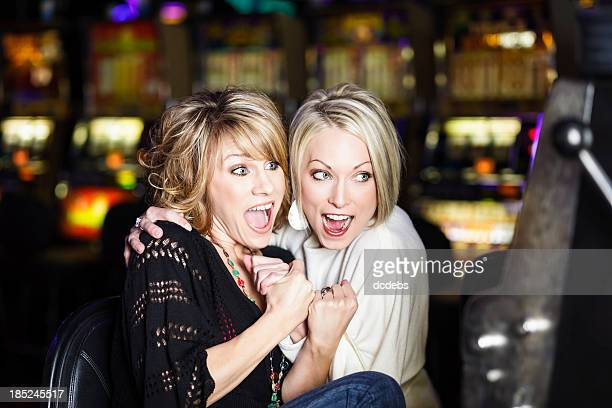 Two women excited while gambling at a casino slot machine