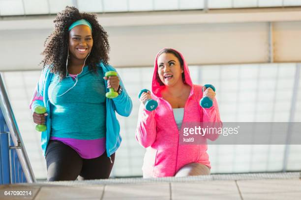 Two women exercising, climbing stairs with hand weights