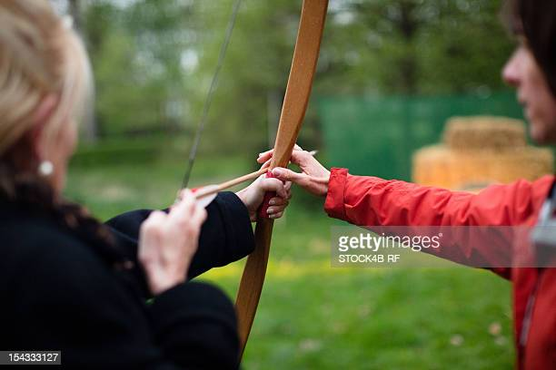 Two women exercising with bow and arrow