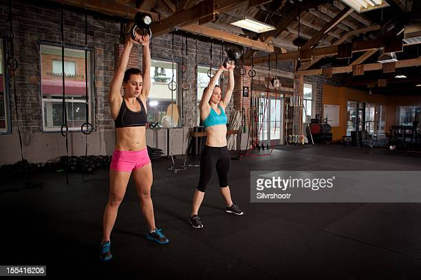 Two women exercising with kettle balls in gym