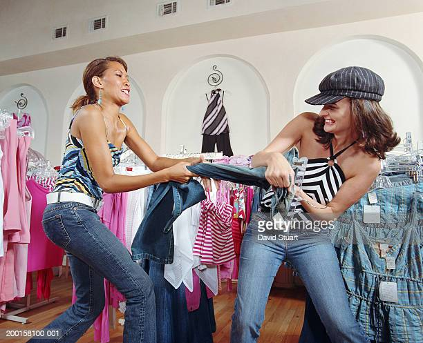 Two women fighting over pair of jeans in boutique, side view