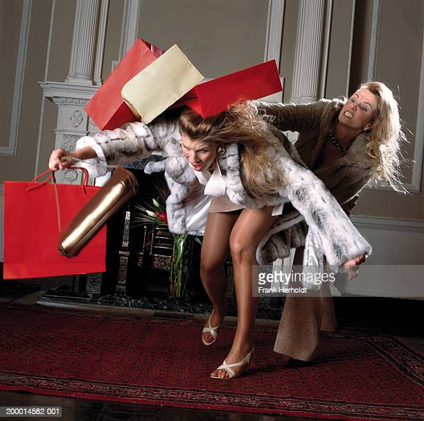Two women fighting with shopping bags, indoors