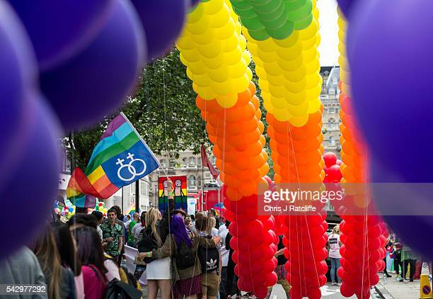 Two women fly a rainbow flag next to a rainbow balloon arch as the LGBT community celebrates Pride in London on June 25 2016 in London England Across...