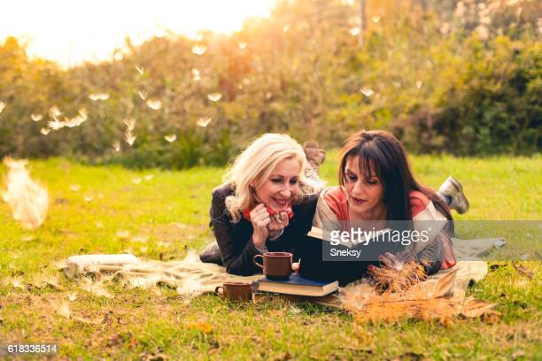 Two women friends reading book in the park