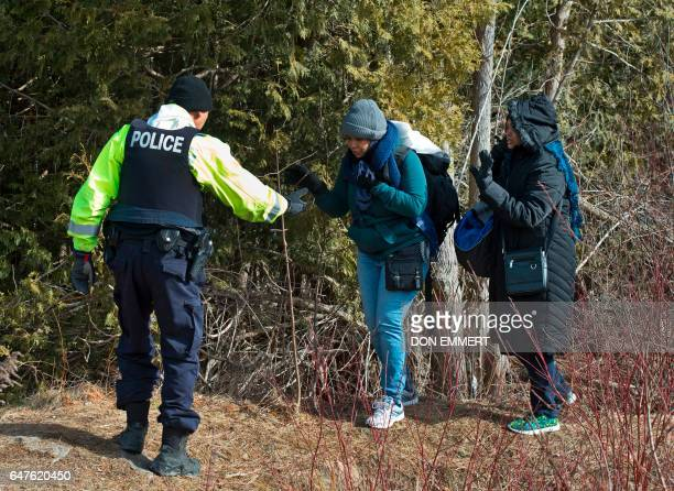 TOPSHOT Two women from Sudan are helped by the RCMP at the US/Canada border February 26 in Champlain NY The women were arrested for crossing the...