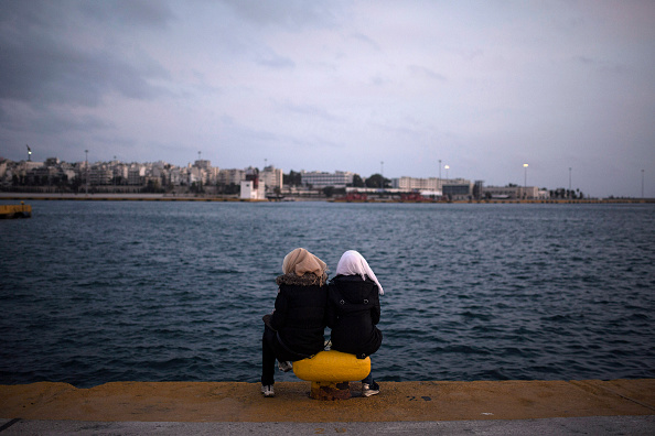 TOPSHOT - Two women from Syria sit facing the sea at Piraeus harbour in Athens, on March 6, 2016. At least 25 migrants including children died on March 6 when their wooden boat capsized in the Aege...