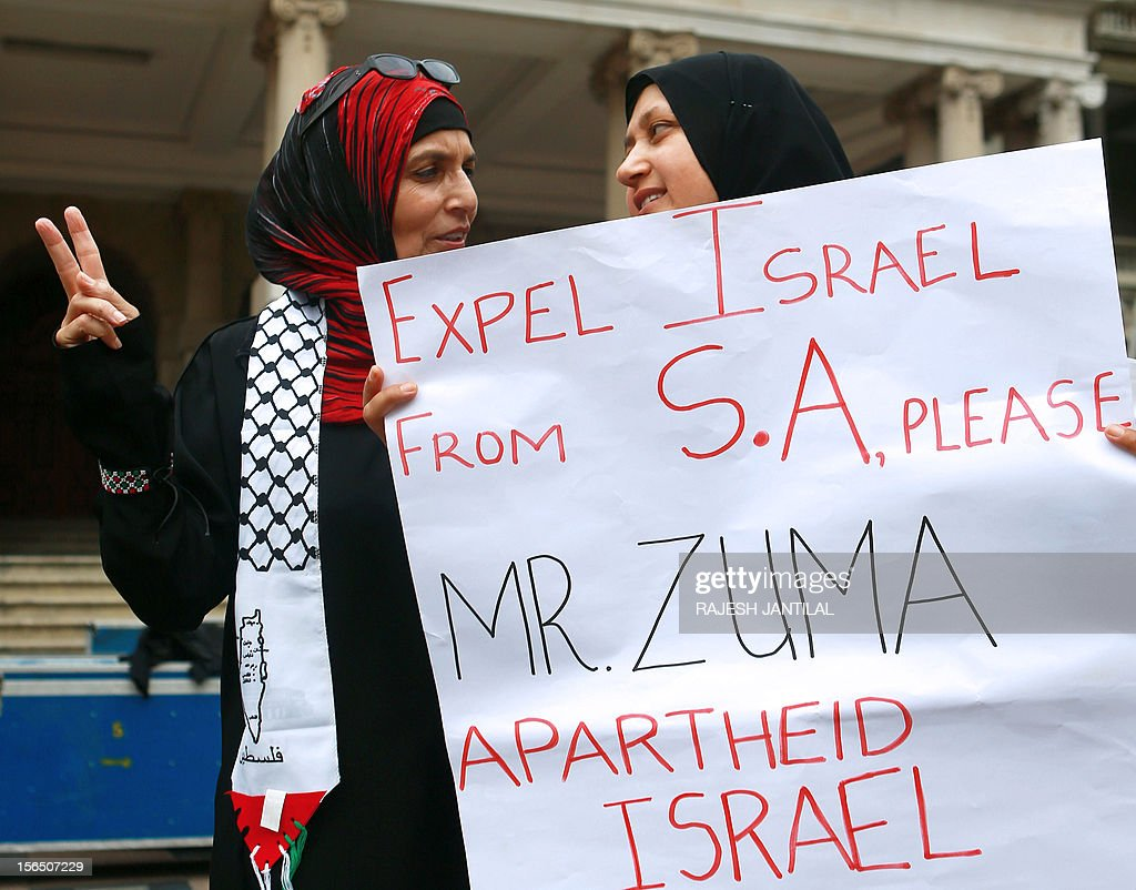 Two women from the Coalition for a Free Palestine (CFP) hold a sign as they gather outside the Durban City hall on November 16, 2012 to protest against the Israeli bonbardment of Gaza.The demonstrators called on South African President Jacob Zuma to recall the South African ambassador in Tel Aviv and to expel the Israeli ambassador. Some of them were singing ' Down with Apartheid Israel Down' and 'Stop the killings of innocent children of Gaza'. AFP PHOTO / RAJESH JANTILAL