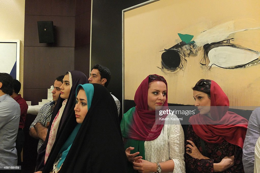 Two women from the Persian Gulf region stand next to spectators during a contemporary art auction by famous Iranian artists in the dinning hall of hotel Azadi on June 28, 2013 in Tehran, Iran.