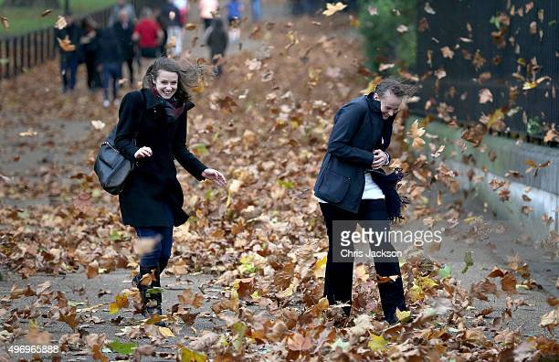 Two women get caught in gusts of wind during a rain storm in Green Park on November 13 2015 in London England