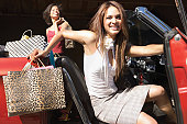 Two women getting out of convertible after shopping