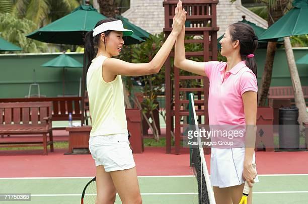 Two women giving high five across tennis net