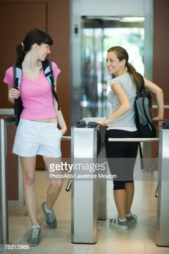 Two women going through turnstile at health club, looking over shoulders at each other