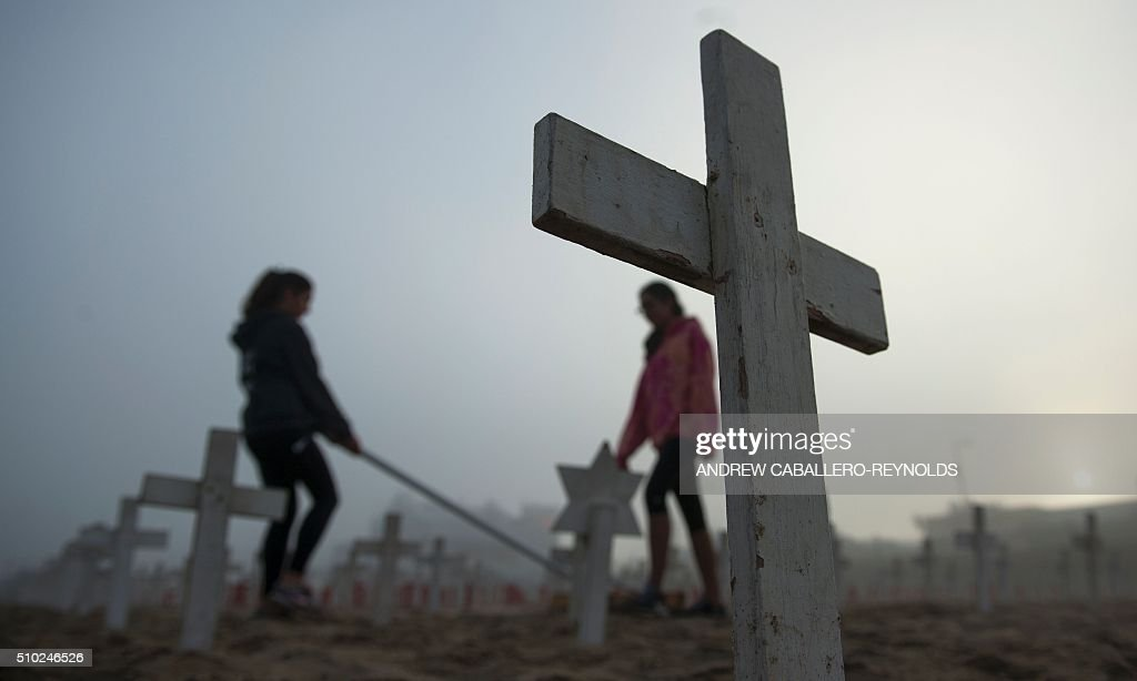 Two women groom the sand around crosses at a peace memorial in Santa Monica, California on February 14, 2016. / AFP / ANDREW CABALLERO-REYNOLDS