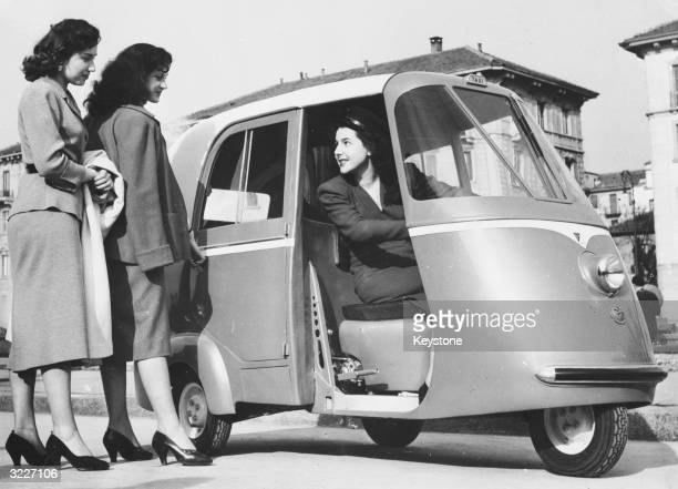 Two women hailing a Piaggio taxiscooter a new type of taxi built for two passengers Milan 18th April 1952 The taxi is the first of a new fleet which...
