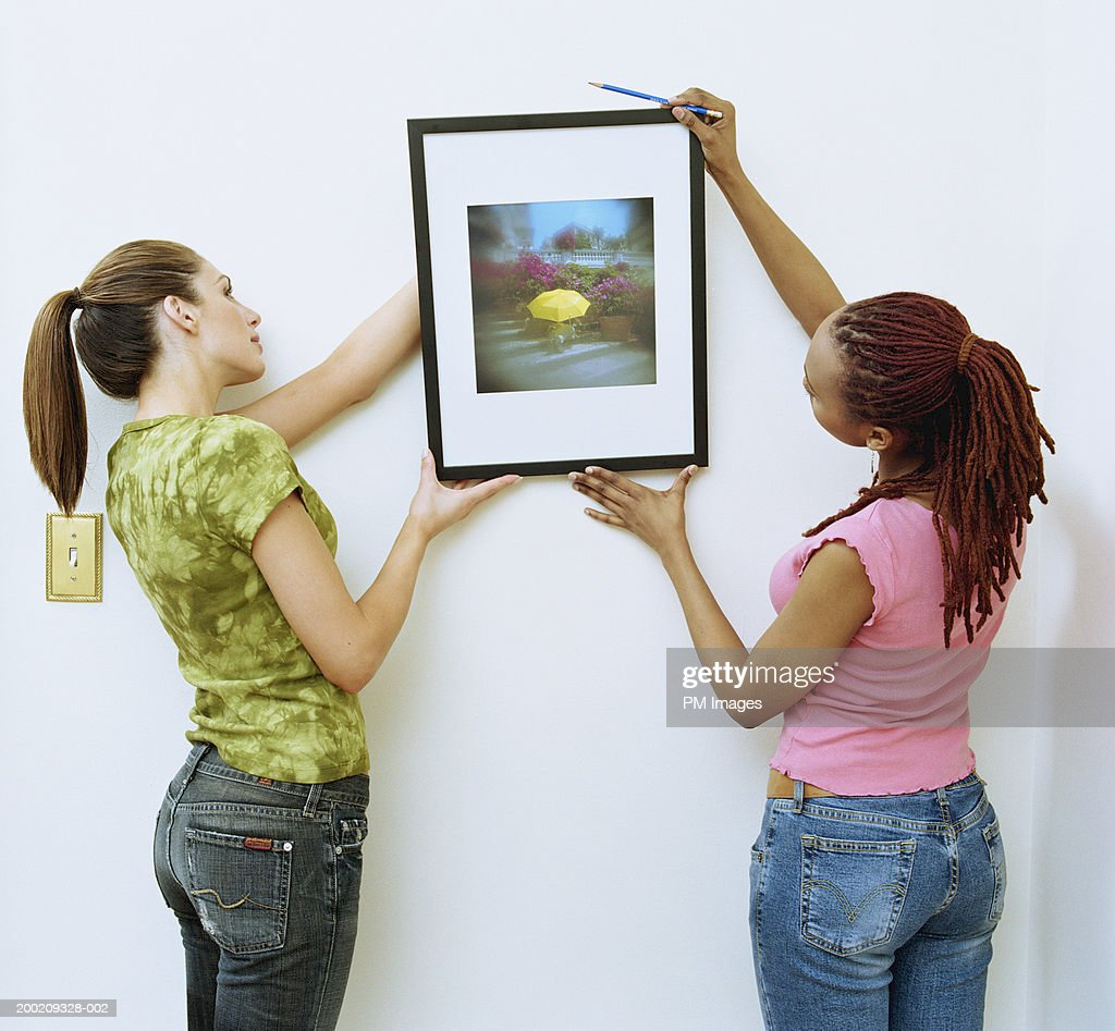 Two women hanging picture on wall : Stock Photo
