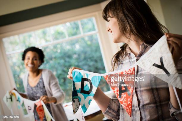 Two women hanging up bunting with lettering, decorating for a party.
