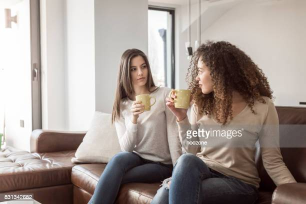 Two women having coffee together on sofa